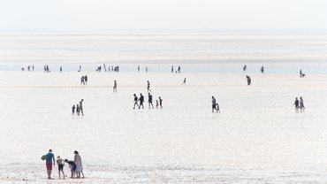 Strandbild mit vielen Spaziergängern bei Ebbe