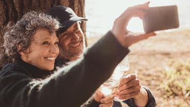 Eine ältere Frau und ein älterer Mann blicken in ein Handy.