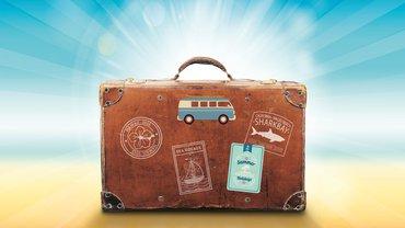 Ein Koffer mit Aufklebern und Stickern am Strand.
