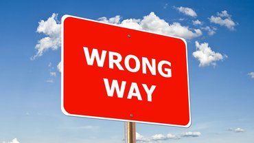 "Ein rotes Schild mit der Aufschrift ""wrong way"" vor blauem Hintergrund"