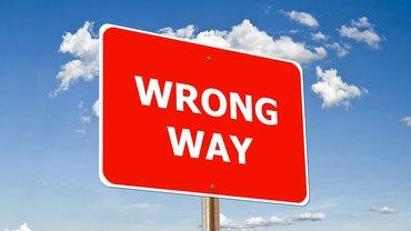 """Ein rotes Schild mit der Aufschrift """"wrong way"""" vor blauem Hintergrund"""